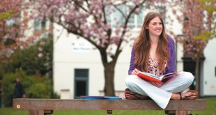 Female-undergraduate-student-sitting-and-reading-on-a-bench-outside-New-Theatre,-University-Park-Cropped-714x335